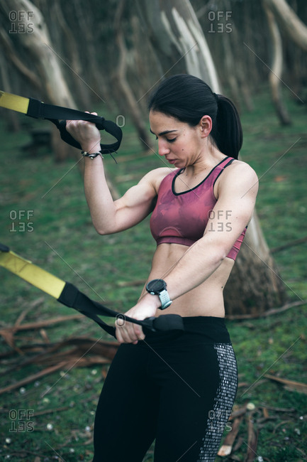 Strong young woman training biceps and triceps with trx suspension fitness straps outdoor