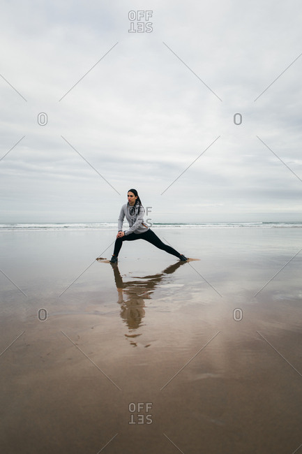 Sporty woman on fitness workout doing leg stretching warming up exercise at the beach in winter