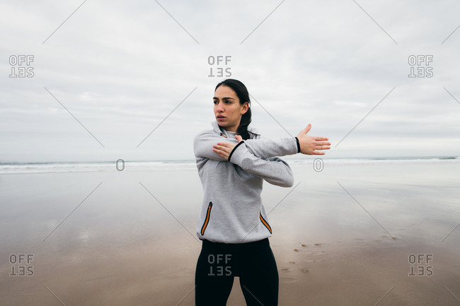 Sporty woman exercising and stretching arms at the beach in winter