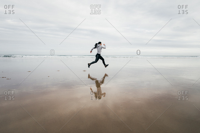 Sporty woman running at the beach in winter