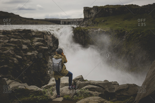 Rearview of woman photographing massive Dettifoss waterfalls in Iceland