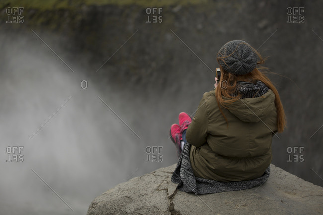 Woman sitting on edge of cliff taking photo of her feet with smart phone at Dettifoss waterfalls in Iceland