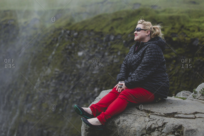 Woman sitting on the edge of a cliff enjoying the view of Dettifoss waterfalls in Iceland