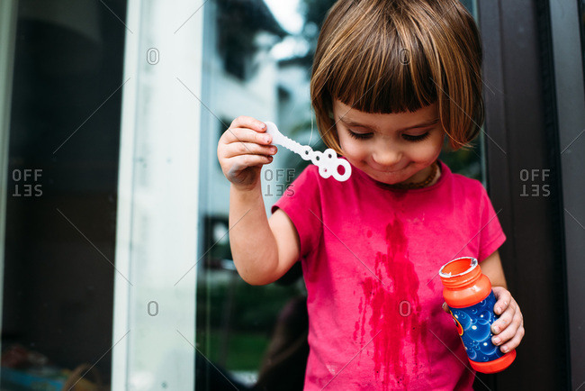 Little girl looking down at spilled liquid while blowing bubbles