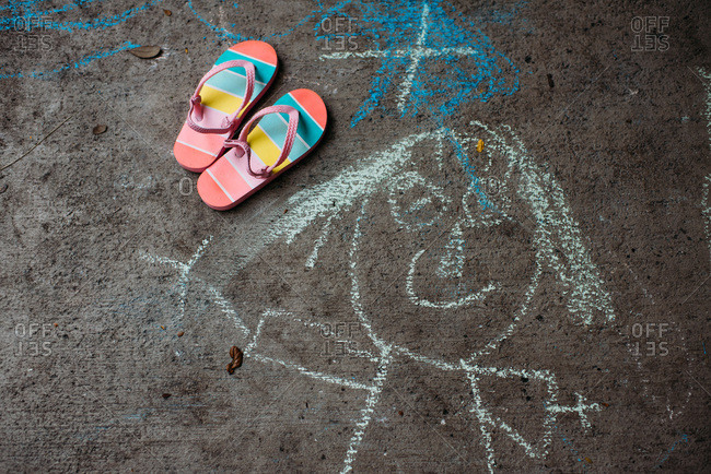 Looking down on a pair of kid's stripy flip flops and a chalk drawing on the pavement
