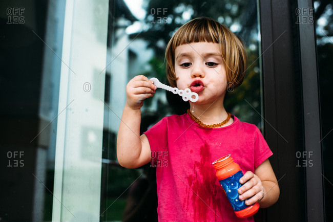 Young girl huffing and puffing trying to blow bubbles