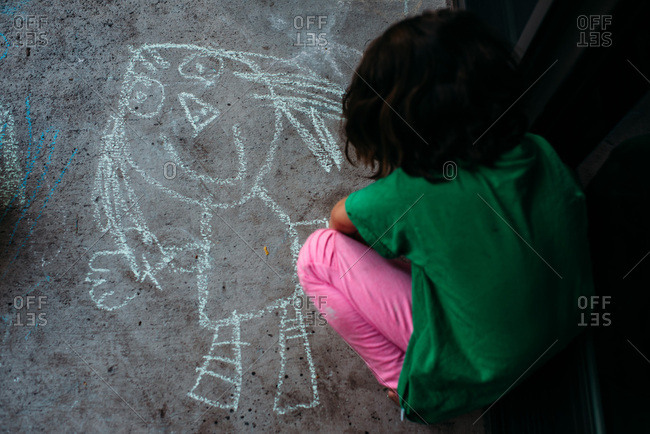 Little girl drawing on the pavement with chalk