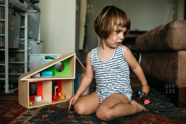 Young girl looking behind distracted while playing with doll house