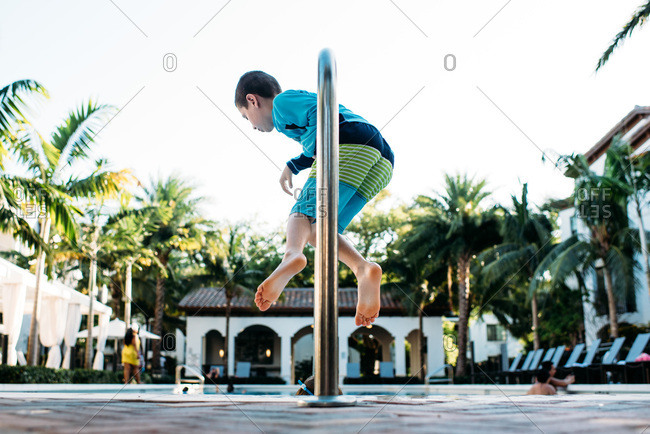 Young boy hanging on railing by side of tropical pool