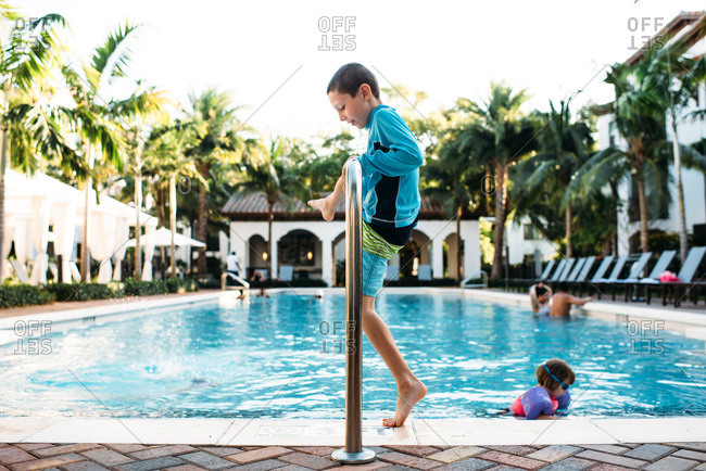 Young boy and little sister playing by the side of a tropical pool