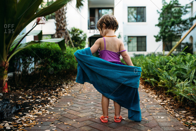 Little girl re-arranging towel around herself after leaving hotel pool
