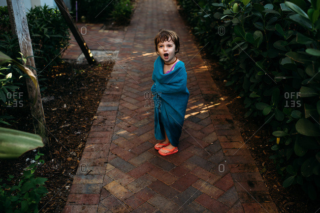 Little girl wrapped in towel objecting to leaving swimming pool