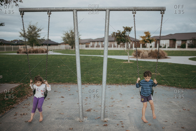 Boy and girl sitting on playground swings