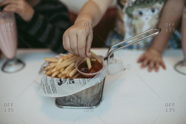 Boy eating fries at cafe