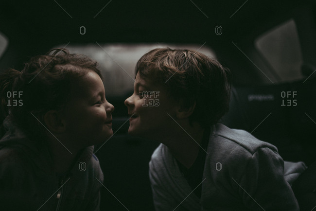 Boy and girl looking at each other in car