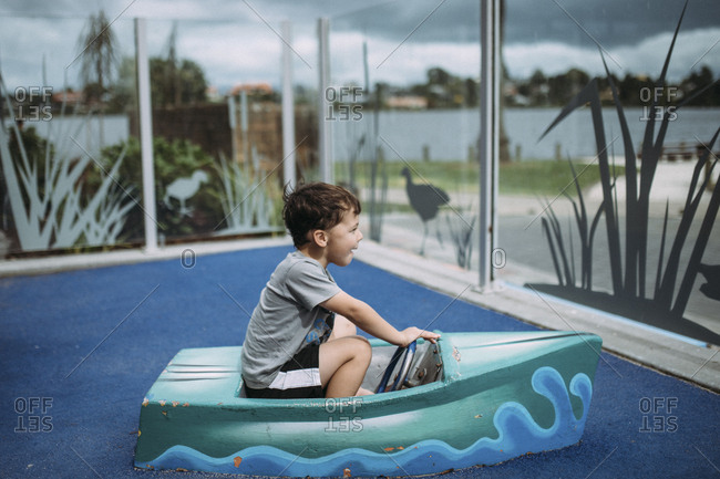 Boy playing in boat at public playground