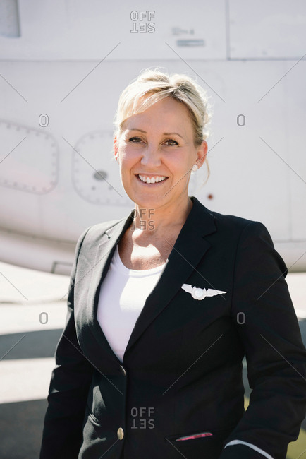 Portrait of confident smiling air stewardess standing against airplane