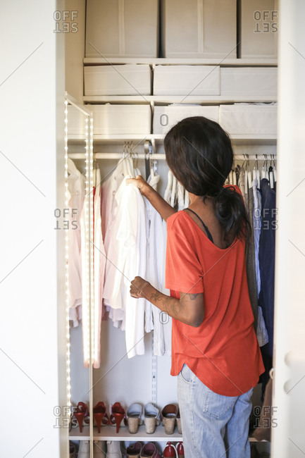 Rear view of woman arranging wardrobe at home