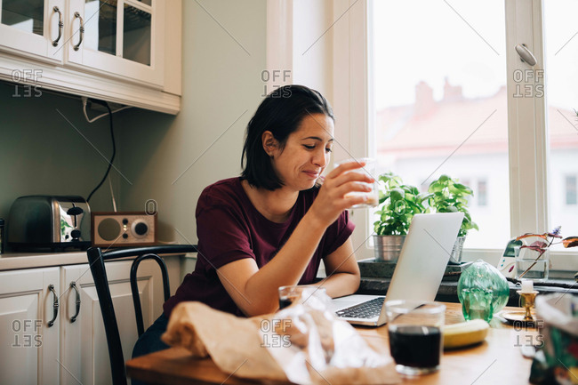 Woman using laptop while having drink at dining table in kitchen