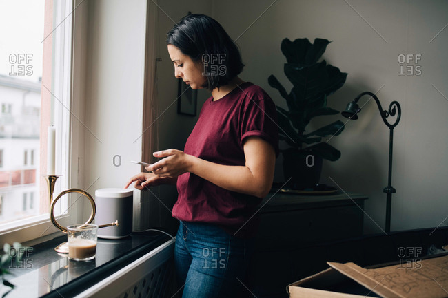 Woman holding smart phone while using equipment by window
