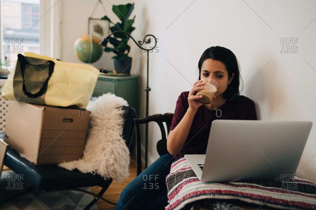 Woman drinking tea while using laptop by wall during relocation of house
