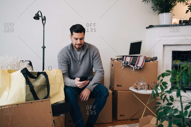 Mid adult man using mobile phone while sitting on box at home
