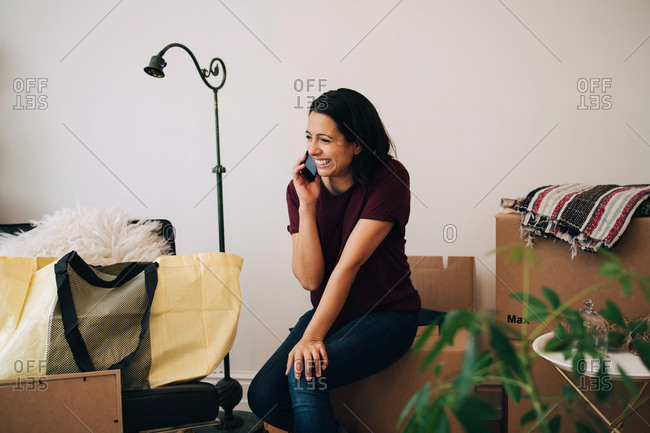 Smiling woman talking on mobile phone while sitting on box against wall