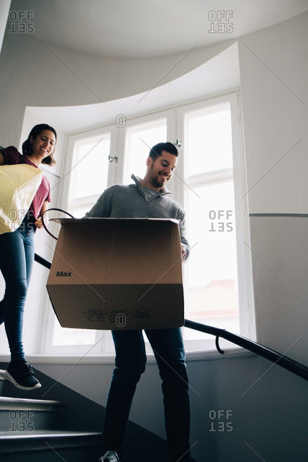 Low angle view of couple carrying box and bag while moving down steps