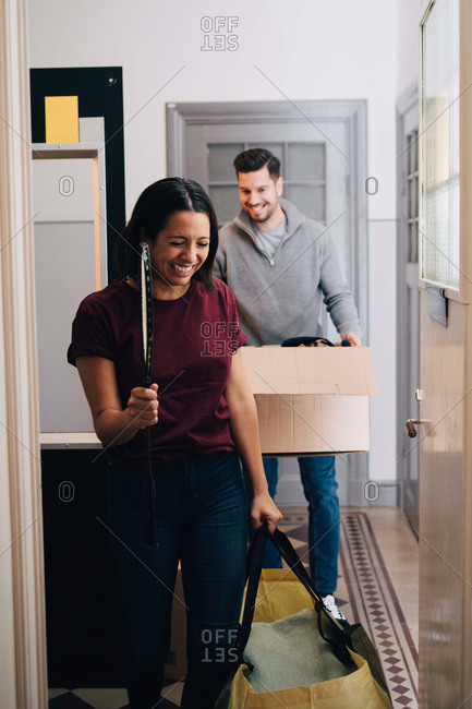 Smiling couple carrying box and bag while walking in corridor at home