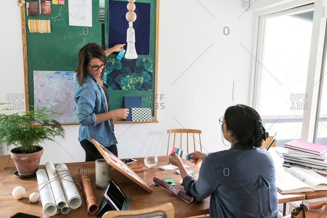 Female design professionals working together in home office