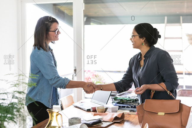 Female colleagues giving handshake while standing at table in home office