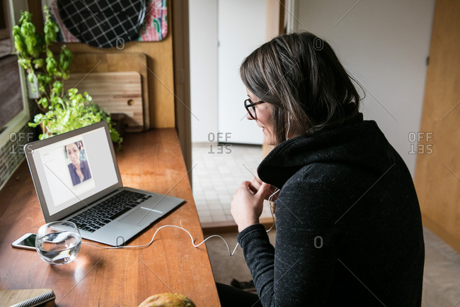 Side view of businesswoman video calling female colleague on laptop in home office