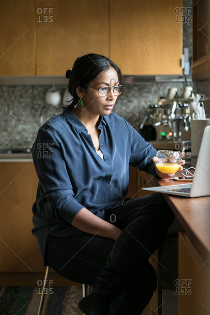 Businesswoman holding juice while using laptop in home office