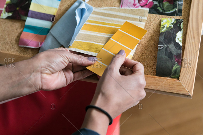 cropped hands of businesswoman holding color swatches in home office