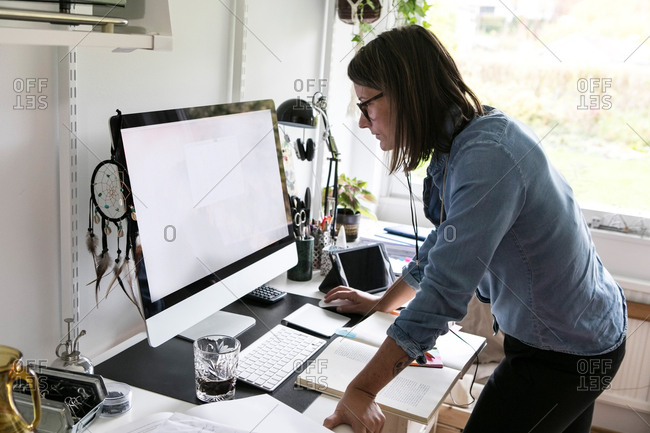 Side view of businesswoman using computer while standing at home