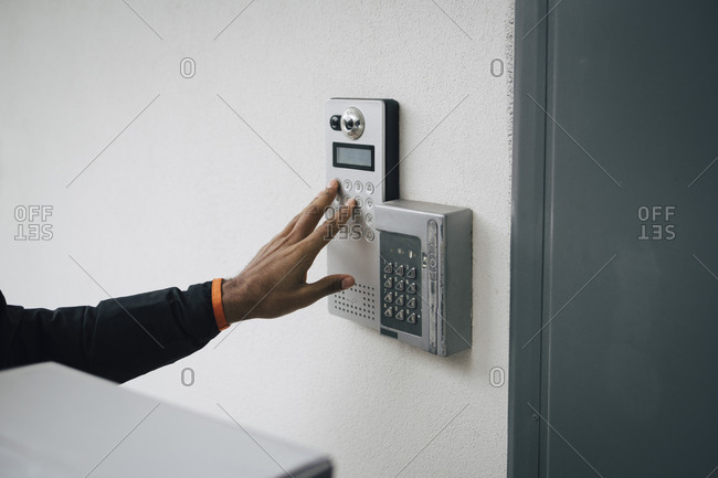 Cropped image of delivery man ringing intercom on wall