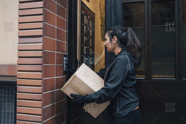 Female messenger ringing intercom while carrying box by closed door