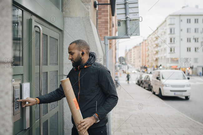 Male messenger holding package while ringing intercom of building