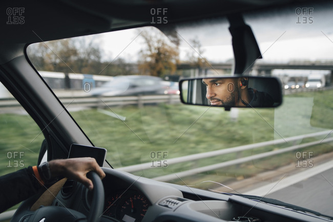 Man is reflecting on rear-view mirror of delivery van