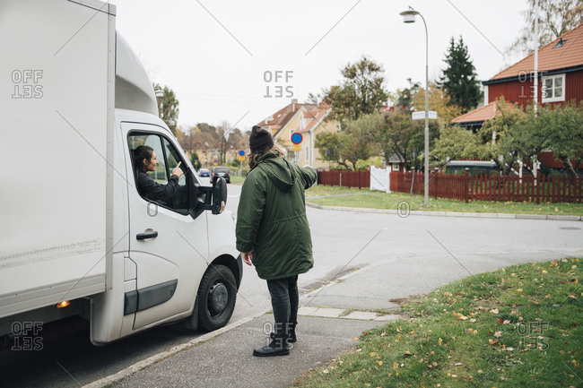 Man directing woman sitting in delivery van on street