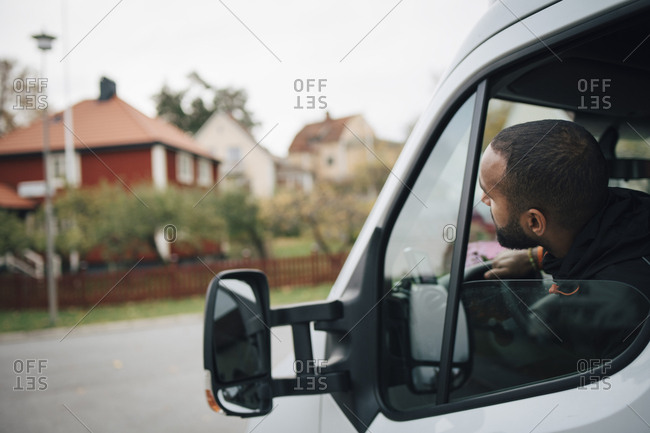 Male worker sitting in delivery van at city