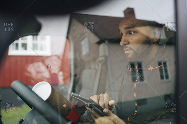 Man holding digital tablet seen through windshield of delivery van