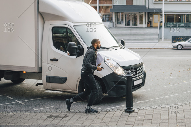 Male messenger with documents running by delivery van on street in city