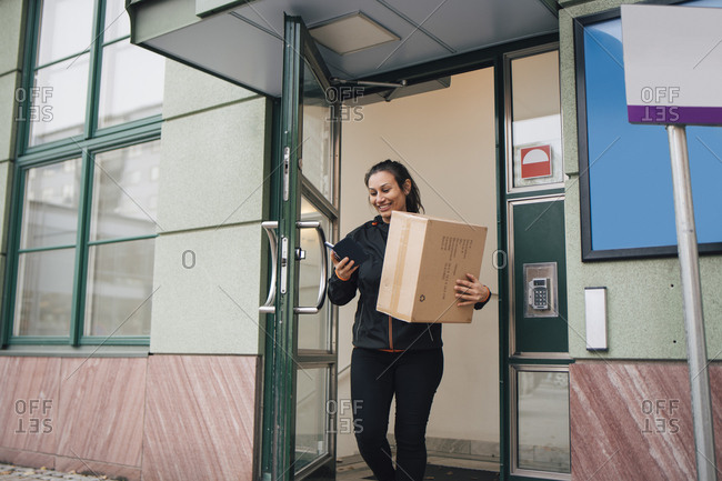 Smiling female worker with box using mobile phone while coming out of building