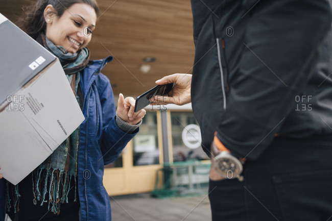 Smiling woman using smart phone to sign for her delivery from messenger