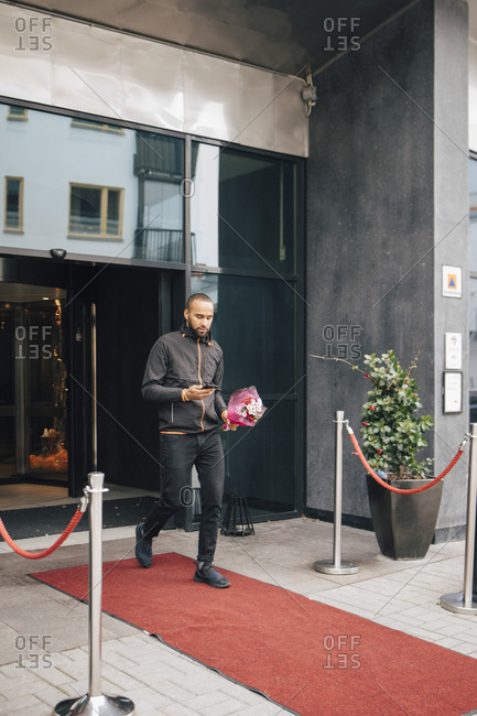 Man with bouquet of flowers using phone while walking on red carpet outside hotel