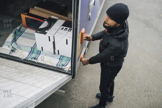 High angle view of worker opening van trunk by pushing buttons on street