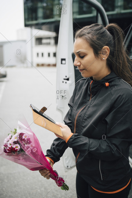 Serious delivery woman looking at mobile phone while holding bouquet of flowers in city