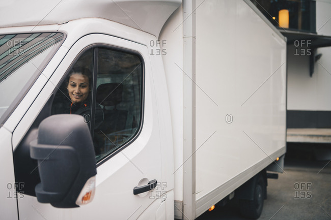 Smiling female worker driving white delivery van in city