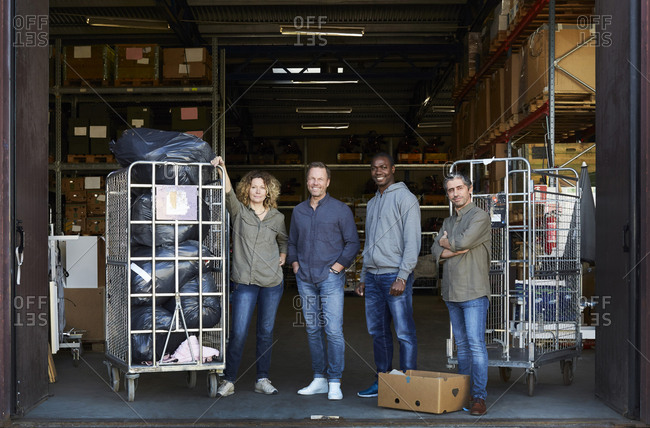 Portrait of smiling coworkers standing amidst carts at warehouse doorway